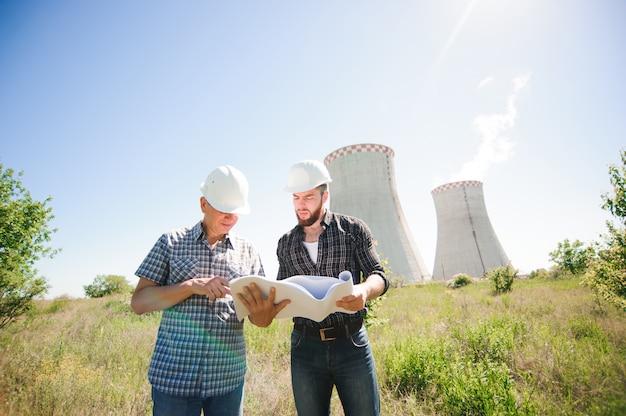 Arquitectos hombres revisando documentos juntos en la planta de energía eléctrica.