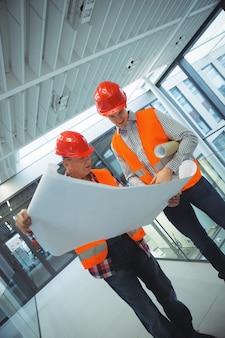 Arquitectos masculinos discutiendo sobre planos en el corredor
