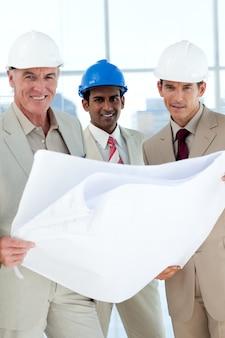 Arquitectos sonrientes con hardhat mirando planos