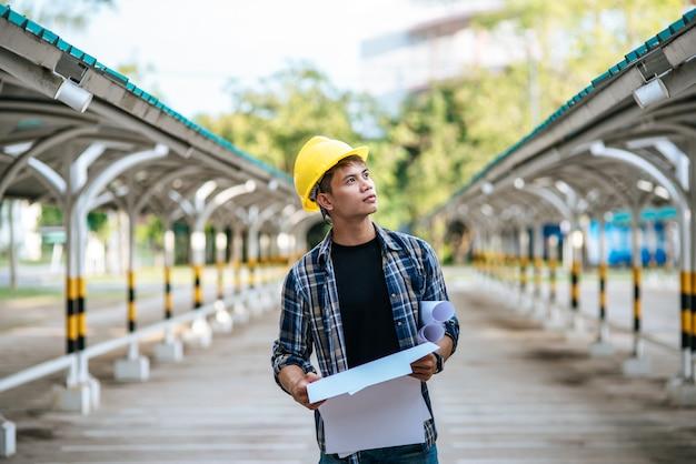 Los arquitectos sostienen el plan de construcción y verifican el trabajo.