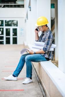 Los arquitectos tienen planos de planta y hablan por teléfono.