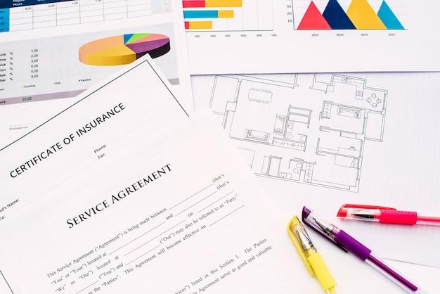 Los arquitectos trabajan en un escritorio sobre planos y documentos financieros de sus edificios.