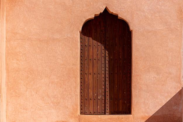 Arquitectura árabe tradicional, puerta de madera de estilo musulmán y pared de arcilla roja.