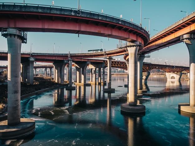 Arquitectura de la ciudad de carreteras y puentes con reflejo de invierno en río