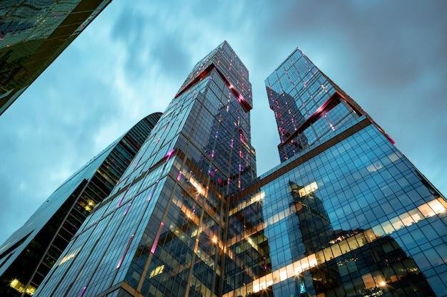 Arquitectura empresarial: rascacielos y senderos de luz. centro de negocios moderno en las luces de la noche.