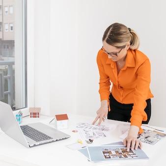 Arquitectura femenina que inspecciona el modelo en el escritorio en la oficina