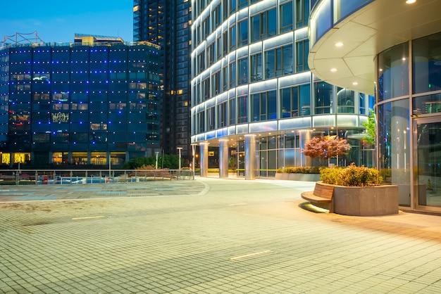 Arquitectura moderna de la pared de cristal del nightscape urbano
