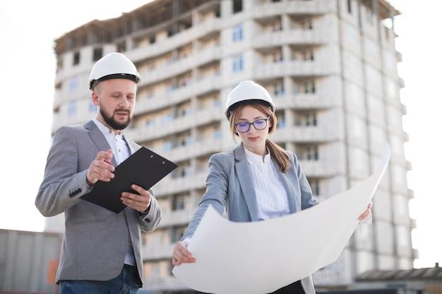 Arquitectura profesional masculina y femenina trabajando juntos en el sitio.