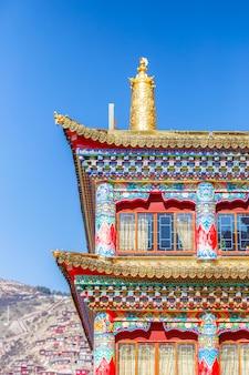 Arquitectura única en las coloridas ventanas de estilo tibetano en la pared roja.