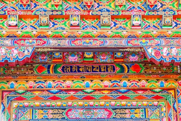 Arquitectura única en la pared hogar de estilo tibetano en pared roja.