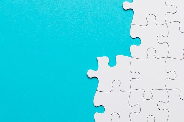Arreglado puzzle blanco sobre superficie azul.