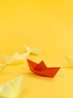Arreglo abstracto con barcos de papel sobre fondo amarillo y espacio de copia