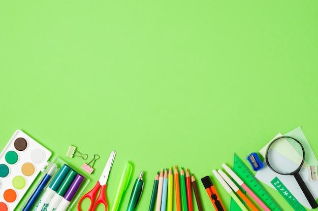 Arreglo de accesorios escolares sobre fondo verde