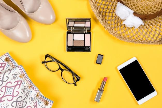 Arreglo de accesorios esenciales de verano para mujer sobre fondo amarillo brillante
