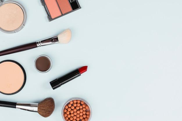 Arreglo de accesorios de maquillaje sobre fondo claro.