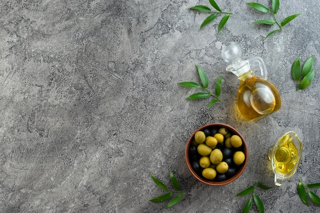Arreglo de aceitunas y aceites sobre fondo de mármol.