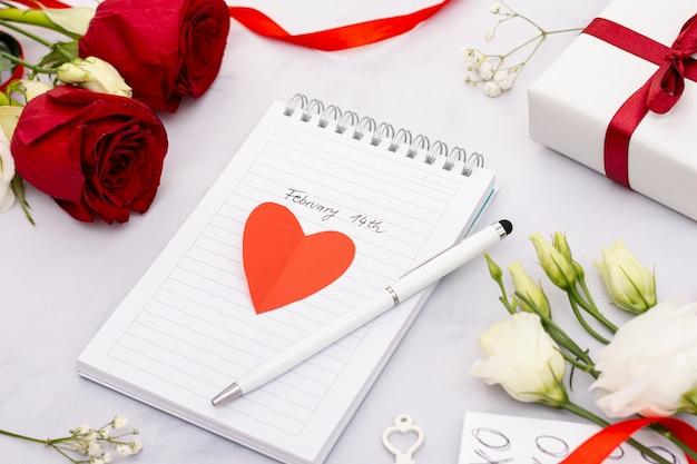 Arreglo de alto ángulo con cuaderno y rosas