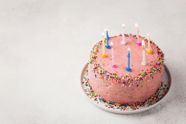 Arreglo de alto ángulo con pastel rosa para fiesta de cumpleaños