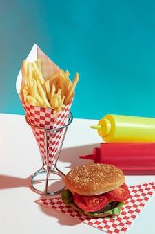 Arreglo de ángulo alto con botellas de salsa y hamburguesa