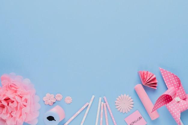 Arreglo de artesanía rosa y equipo sobre fondo azul.