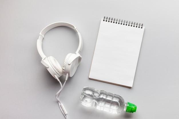Arreglo con auriculares, cuaderno y botella de agua.