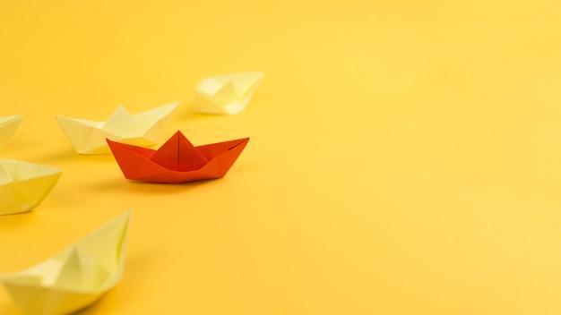 Arreglo con barcos de papel sobre fondo amarillo y espacio de copia