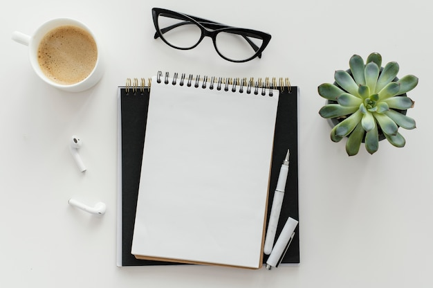 Arreglo con bloc de notas vacío en el escritorio