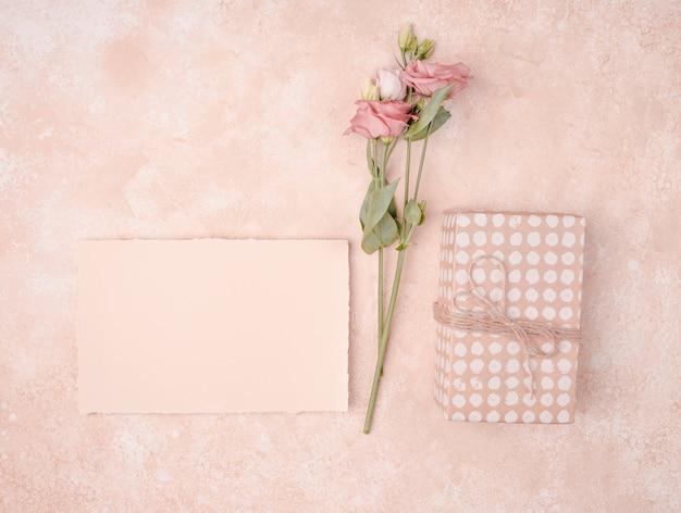 Arreglo de boda con invitación y flores.