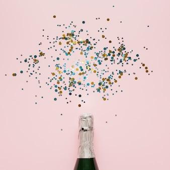 Arreglo de botella de champagne y confeti de colores.