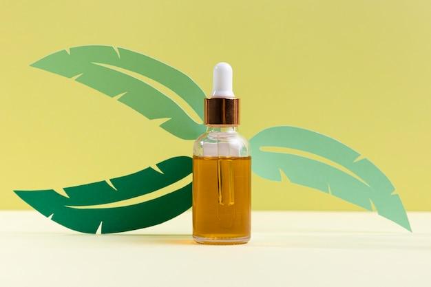 Arreglo de botella cosmética con planta