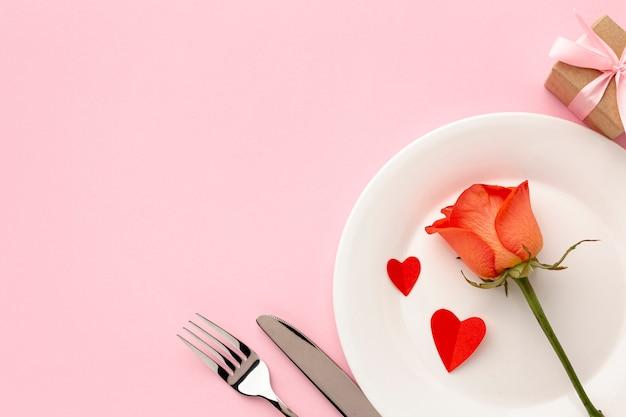 Arreglo para la cena del día de san valentín sobre fondo rosa con rosa naranja