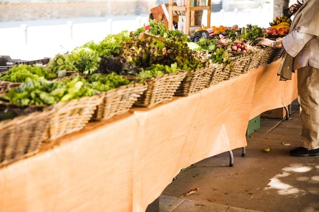 Arreglo de la cesta de verduras en una fila en el mercado local de la calle