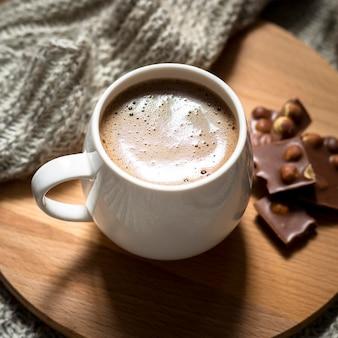 Arreglo de chocolate y café de alto ángulo sobre tabla de madera