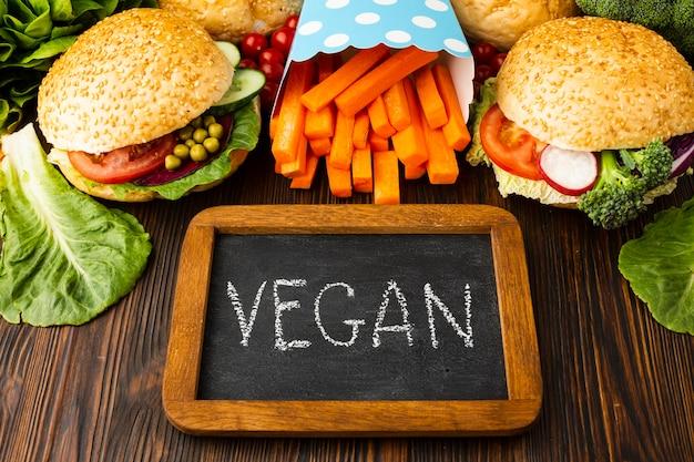 Arreglo de comida sana de alto ángulo con letras veganas en pizarra