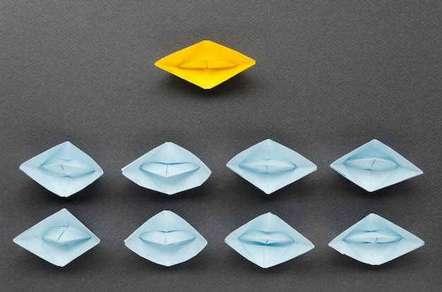 Arreglo para el concepto de individualidad con barcos de papel sobre fondo negro