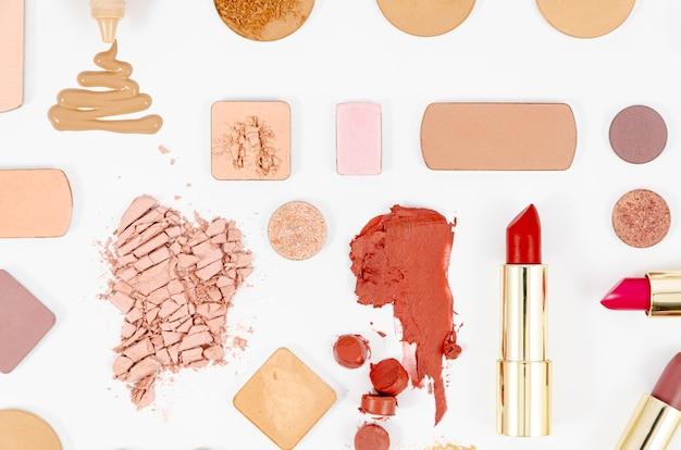 Arreglo de cosméticos coloridos sobre fondo blanco.