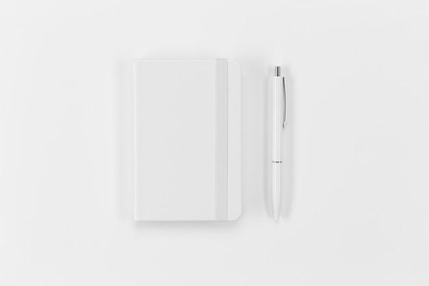 Arreglo de cuaderno y bolígrafo de vista superior