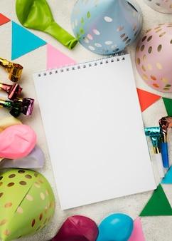 Arreglo con cuaderno y sombreros de fiesta