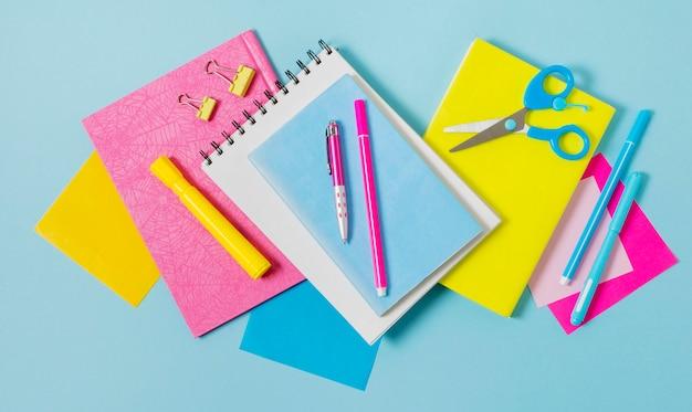 Arreglo de cuadernos y bolígrafos