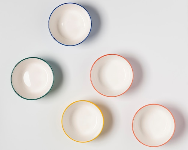 Arreglo de cuencos de colores sobre fondo blanco.