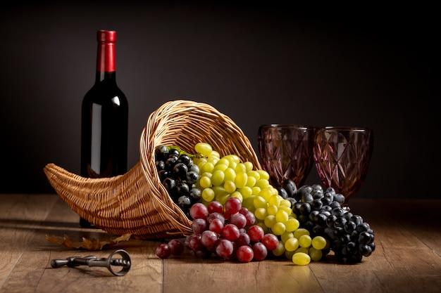 Arreglo de cuerno de la abundancia con deliciosas comidas y una botella de vino.
