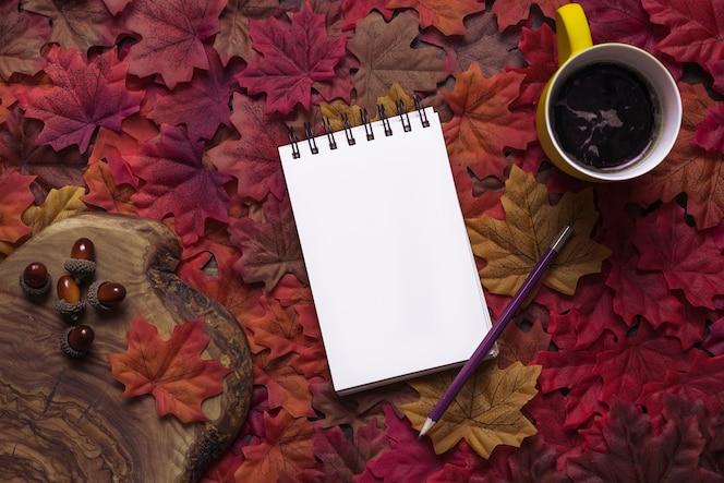Arreglo de otoño con bloc de notas y bebidas