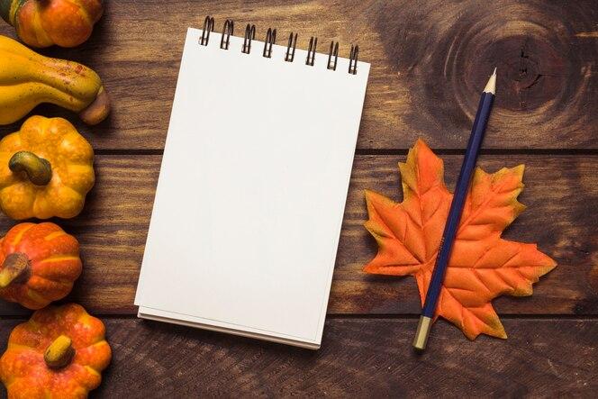 Arreglo de otoño con bloc de notas y calabazas