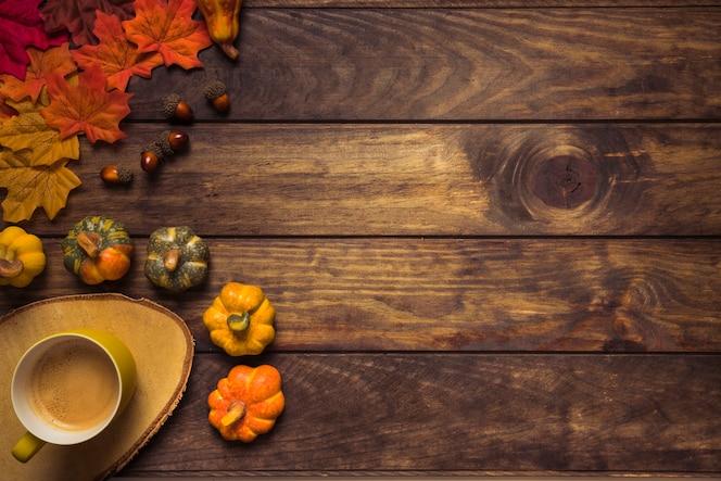 Arreglo de otoño con hojas y bebida caliente