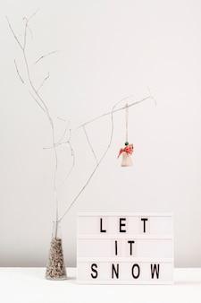 Arreglo con la decoración del árbol y dejar que nieve signo