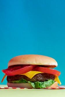 Arreglo con deliciosa hamburguesa con queso y fondo azul