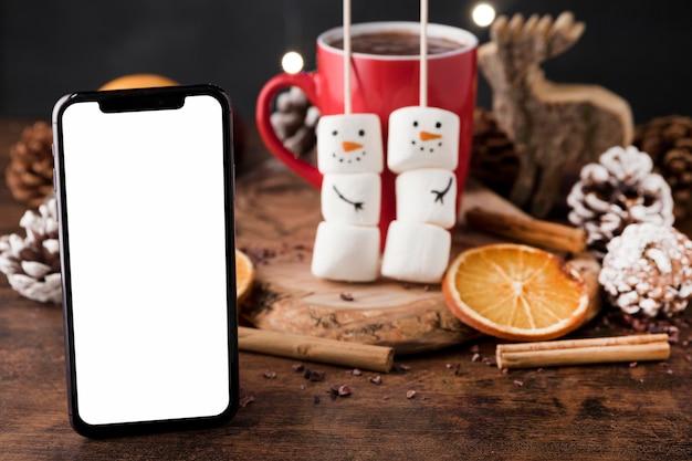 Arreglo de una deliciosa taza navideña de chocolate caliente y un teléfono inteligente vacío