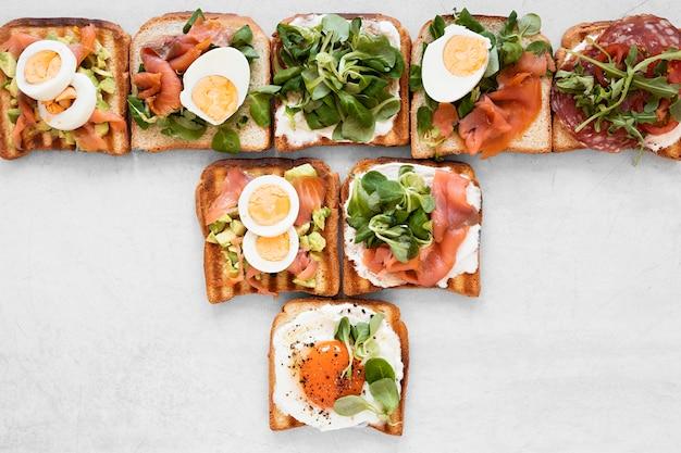 Arreglo de deliciosos sandwiches sobre fondo blanco.