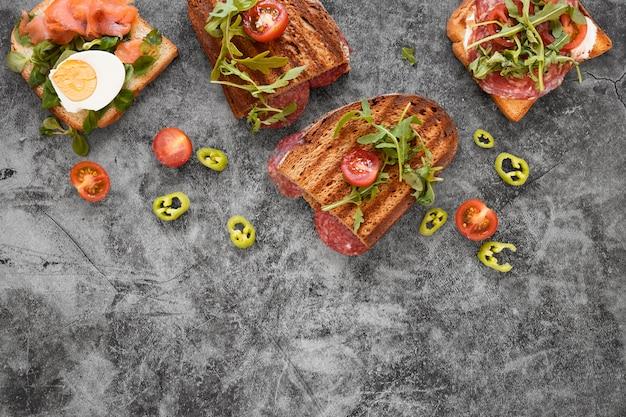 Arreglo de deliciosos sandwiches sobre fondo de cemento con espacio de copia