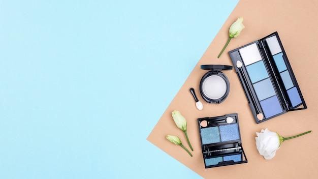 Arreglo de diferentes cosméticos con copia espacio sobre fondo azul.